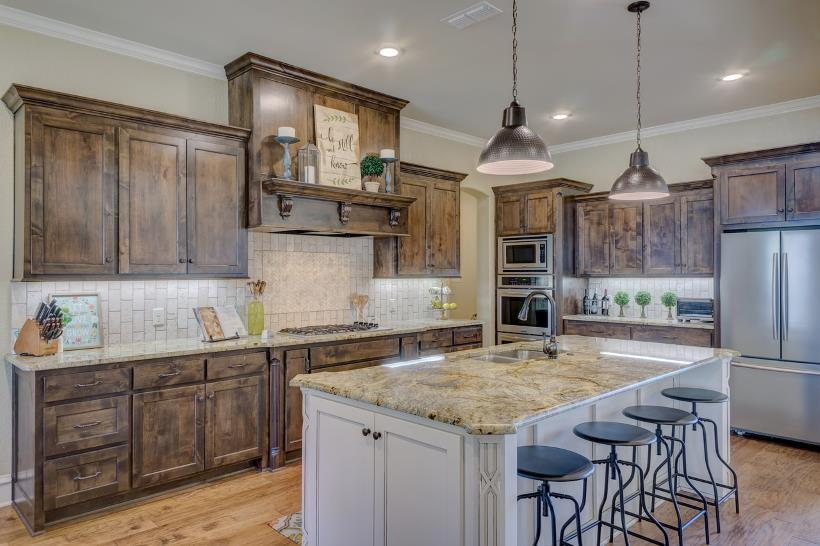 Stainless steel kitchen appliances paired with rustic, distressed cabinetry